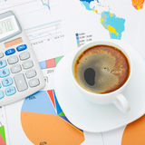 Coffee cup and calculator over financial documents - close up studio shot Stock Photo