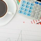 Coffee cup and calculator over financial documents Royalty Free Stock Images
