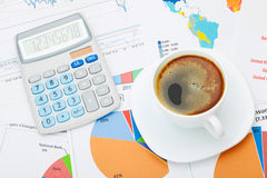 Coffee cup and calculator over financial documents - studio shot Stock Photo