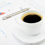 Coffee cup and calculator over some financial charts - close up shot Stock Images