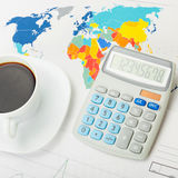 Coffee cup and calculator over world map - close up studio shot Royalty Free Stock Photo