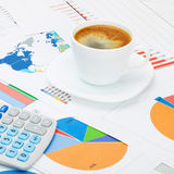Coffee cup and calculator over world map and financial charts - close up shot Royalty Free Stock Image