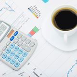 Coffee cup and calculator over world map and financial charts - close up shot. Coffee cup and neat calculator over world map and financial charts - close up shot stock photo