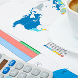 Coffee cup and calculator over world map and financial graphs - close up shot Royalty Free Stock Photos