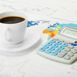 Coffee cup and calculator over world map and some financial chart - close up Royalty Free Stock Images
