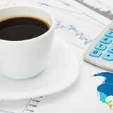 Coffee cup and calculator over world map and some financial chart - close up Royalty Free Stock Photo