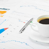 Coffee cup and calculator over world map and some financial chart - close up shot Stock Image