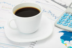 Coffee cup and calculator over world map and some financial charts - business concept Royalty Free Stock Photo