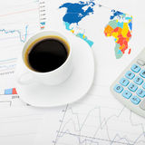 Coffee cup and calculator over world map and stock market charts - close up shot Stock Photo