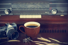 Coffee cup and camera film on retro radio background Stock Photos