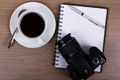 Coffee cup and camera on a wooden surface Royalty Free Stock Photography