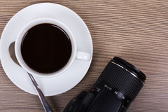 Coffee cup and camera on a wooden surface Stock Image