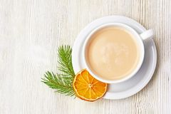 Coffee Cup cappuccino and saucer on a light wooden background de. Corated with fir branch and dried orange. Christmas morning Royalty Free Stock Image