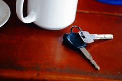 Coffee cup and car keys. White coffee mug on wooden table next to car keys Royalty Free Stock Image