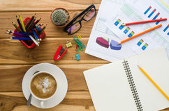Coffee cup, chart, pen, notebook and accessory for work on wooden table Stock Photos