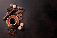 Coffee cup, chocolate and macaroons on old kitchen table. Coffee cup, beans, chocolate and macaroons on old kitchen table. Top view with copyspace for your text stock images