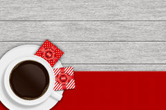 Coffee cup with christmas presents lying on wooden desk Stock Image