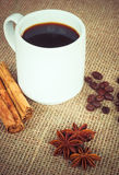 Coffee cup with cinnamon, anise and beans Royalty Free Stock Images