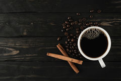 Coffee cup and cinnamon on black wood. stock photos
