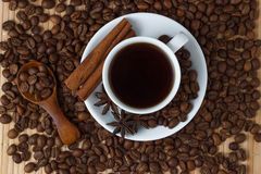 Coffee in a cup with cinnamon sticks and anise on the background of coffee beans.  Stock Images