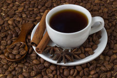 Coffee in a cup with cinnamon sticks and anise on the background of coffee beans.  Royalty Free Stock Photo