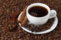 Coffee in a cup with cinnamon sticks on the background of coffee beans Stock Image