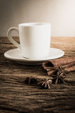 Coffee cup, cinnamon sticks on wooden table Royalty Free Stock Photography
