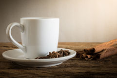 Coffee cup, cinnamon sticks on wooden table Stock Photo