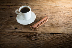 Coffee cup, cinnamon sticks on wooden table Stock Images