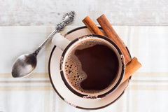 Coffee cup with cinnamon top view. Coffee / Hot chocolate with cinnamon stick and teaspoon Royalty Free Stock Photography