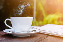 coffee cup clock and news paper on old wooden table nature backg Royalty Free Stock Images