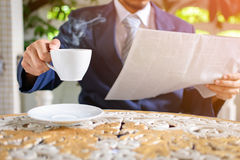 Coffee cup clock and newspaper work on table Stock Image