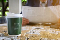 Coffee cup clock and newspaper work on table Royalty Free Stock Images