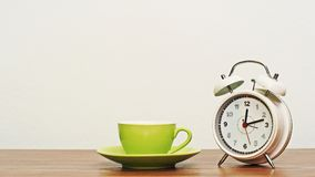 Coffee cup with clock on wooden table Stock Image