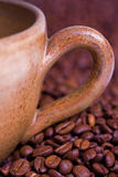 Coffee cup close up. Close up of coffee cup handle and roasted coffee beans stock images