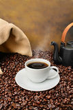 Coffee cup close-up over roasted beans. Old fashioned coffee brewing composition with a full white coffee cup, teapot and coffee bag over roasted coffee beans royalty free stock photos