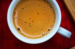 Coffee cup. Close up of a white coffee cup on a red blurry surface Stock Photography