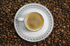 Coffee cup on coffee bean background. Top view Royalty Free Stock Photo