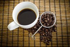 Coffee cup and coffee bean on a wooden table Stock Images