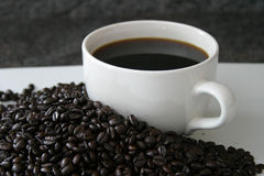 Coffee cup with coffee beans. White coffee cup with coffee beans on a white plate Stock Image