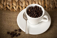 Coffee cup and coffee beans. Coffee cup, coffee beans and a sppon on a plate Royalty Free Stock Photos