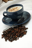 Coffee cup and coffee beans. Coffee cup next to a pile of coffee beans royalty free stock image
