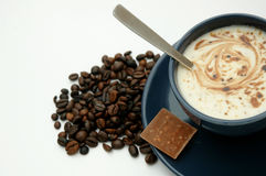 Coffee cup and coffee beans. Coffee cup next to a pile of coffee beans, served with a chocolate bar stock photography
