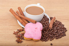 Coffee cup with coffee beans ans sweet cake on a wooden background Stock Image
