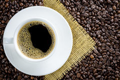 Coffee cup on coffee beans background Stock Photos