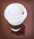 Coffee cup with Coffee Beans on brown background. Takeaway Royalty Free Stock Photos