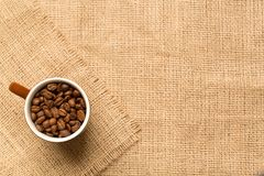Coffee cup and coffee beans on the burlap. Top view. Coffee cup and coffee beans on brown burlap. Top view stock image