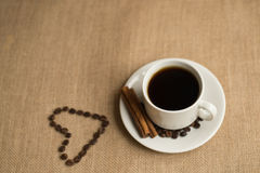 Coffee cup with coffee beans on burlap royalty free stock photography