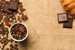 Coffee cup and ingredients on burlap background royalty free stock image