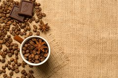 Coffee cup and ingredients on burlap background. Coffee cup and coffee beans, chocolate, anise on brown burlap. Top view stock photos
